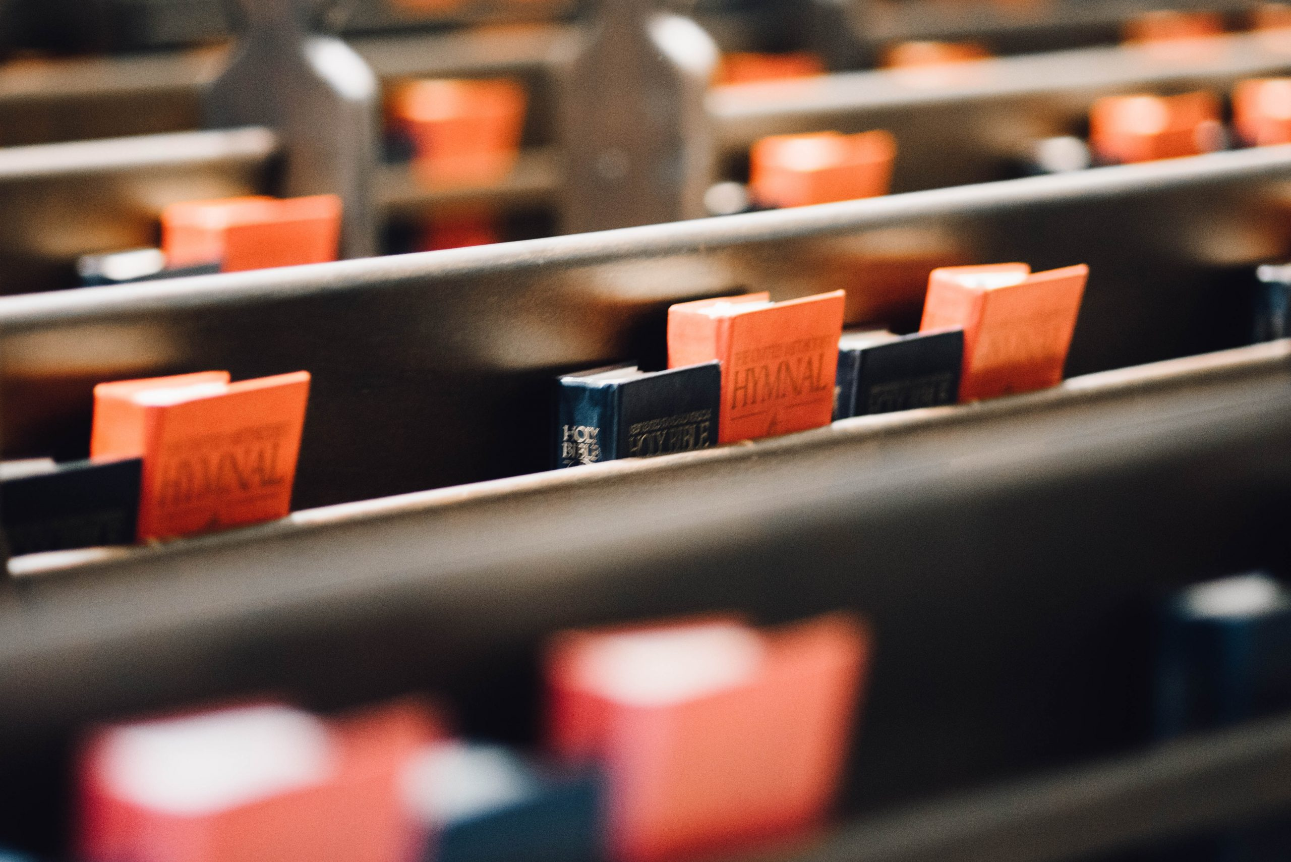 Close up image of pews in a church with Bibles and Hymns on then
