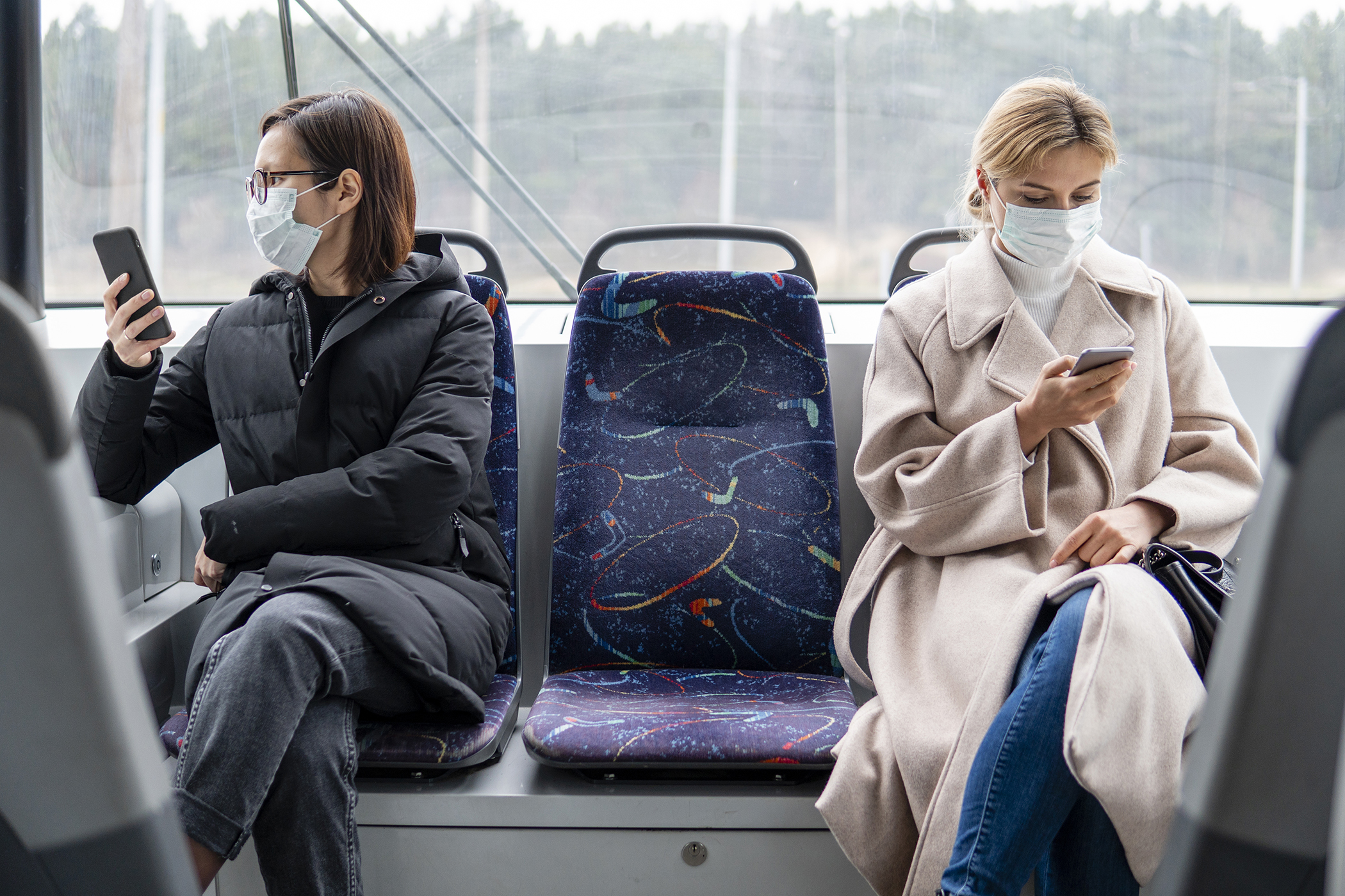 two people sitting on a bus with masks on on their phone