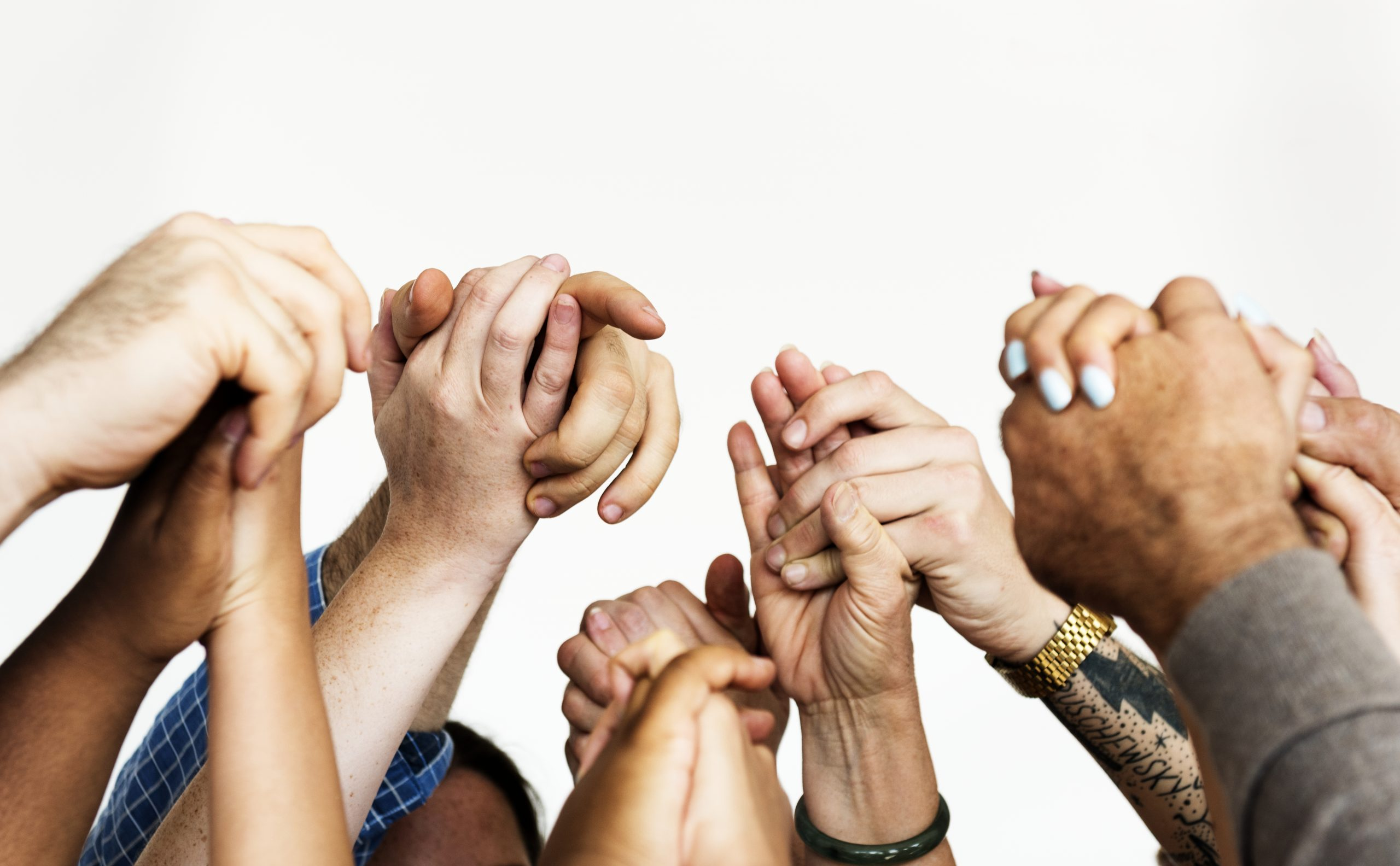 closeup of multiracial people holding hands