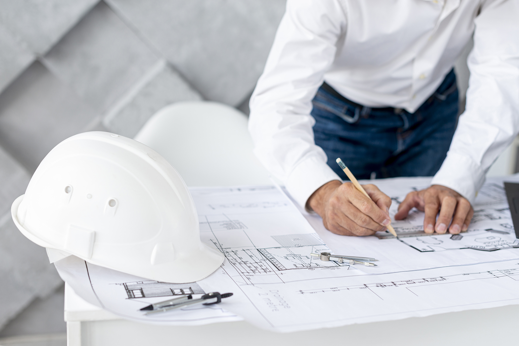 Man writing on a white blue print with construction hats