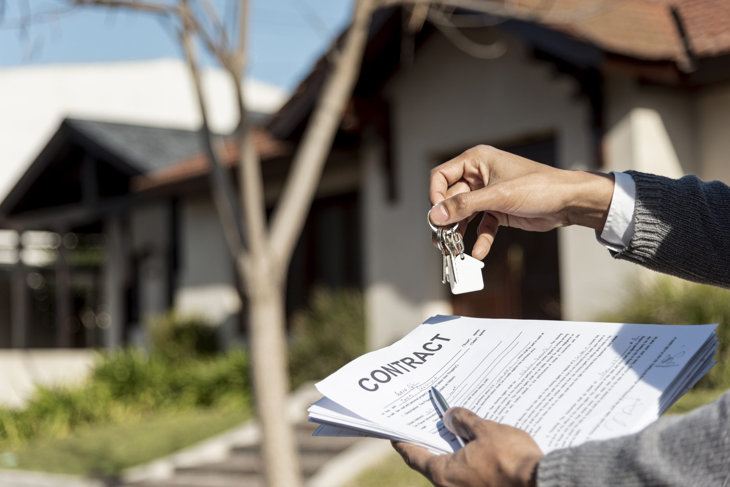 person holding . a contract and keys in front of a house