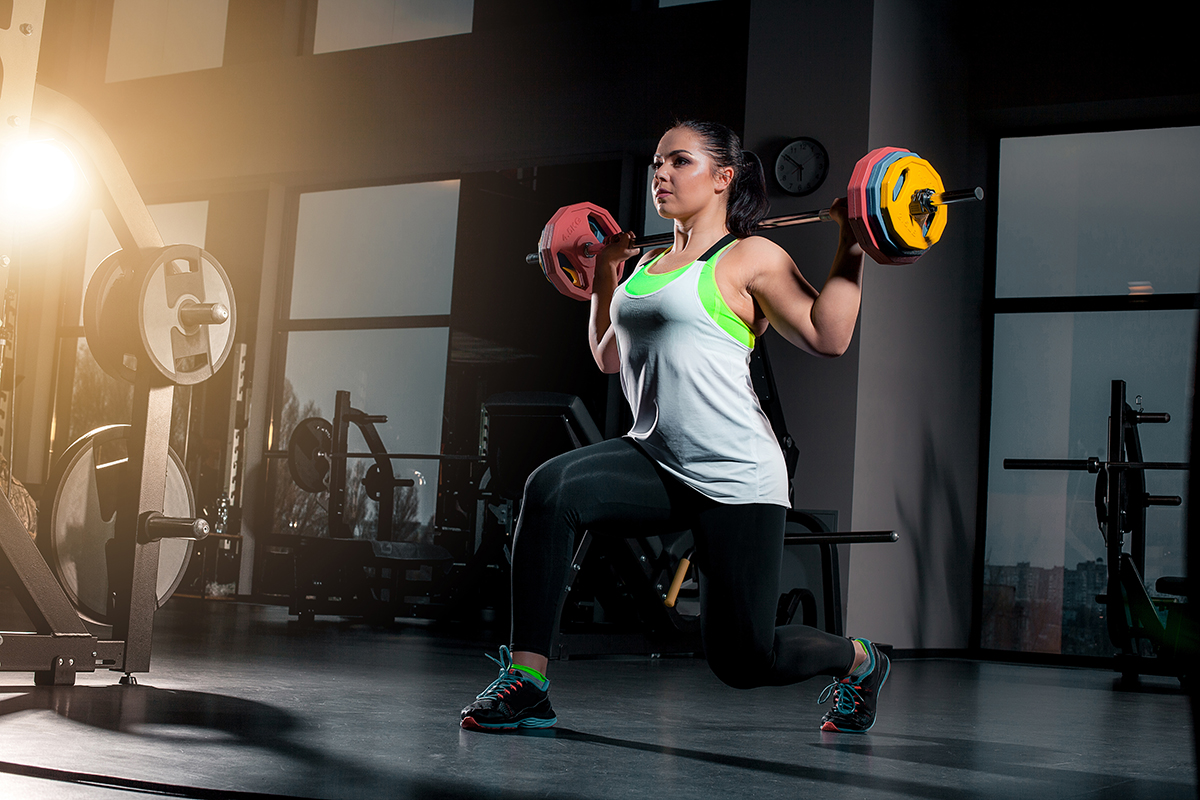 Fit young woman lifting barbells looking focused, working out at a gym